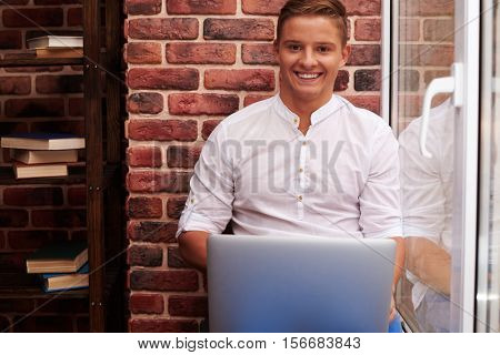 Close-up of positive handsome young man looking at the camera while using silver laptop. Smiling softly while using laptop