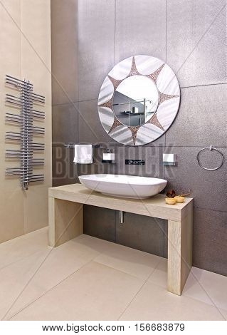 Modern bathroom interior with sparkling tiles and oval mirror