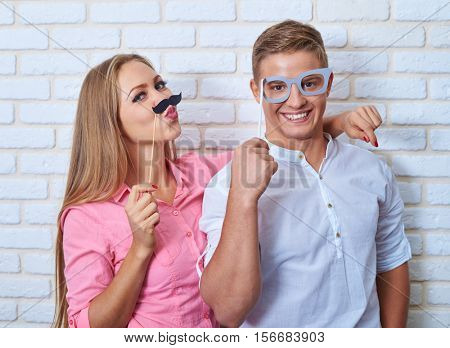 Mid shot of embracing couple, with facial expressions posing with paper sticks. Beautiful young couple is holding sticks, looking at camera and smiling over brick wall background