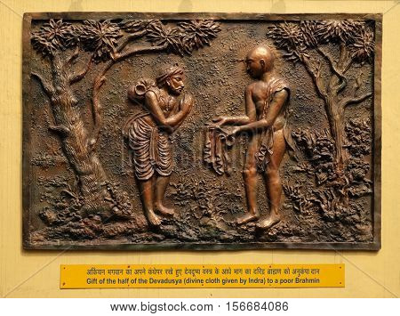 KOLKATA,INDIA - FEBRUARY 09: Gift of the half of the Devadusya (divine cloth given by Indra) to a poor Brahmin, Street bas relief on the wall of Jain Temple in Kolkata, India on February 09,2016.
