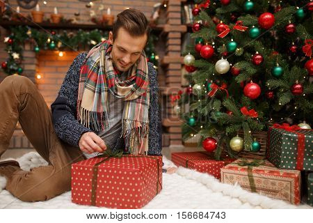 Young man opens Christmas gifts on background of Christmas tree