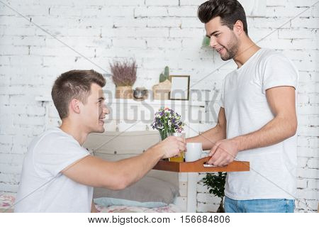 Showing love. Overjoyed young man receiving nice breakfast from his handsome boyfriend holding a tray and standing in bedroom