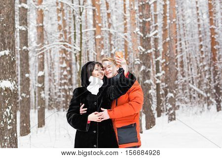 people, season, love, technology and leisure concept - happy couple taking photo with smartphone on over winter background.