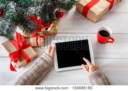 Christmas online shopping top view on wood. Female buyer touch screen of tablet, copy space. Woman has coffee, buys presents near xmas tree, among gift boxes. Winter holidays sales background