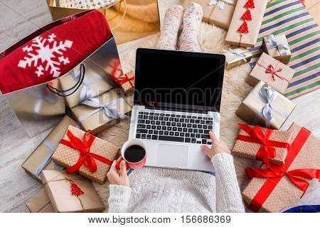 Christmas online shopping top view. Female buyer makes order on laptop, copy space on screen. Woman buy presents, prepare to xmas, among gift boxes and packages. Winter holidays sales