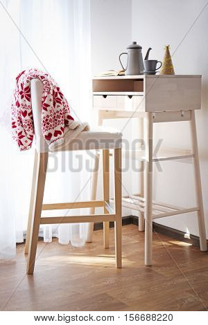 Wooden table and stool in room interior