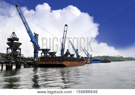 unloading coal from barge to hopper at the coal port
