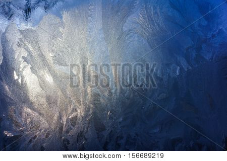 Frosty Pattern on Glass Made of Ice Crystals, Low Temperature, Natural Blue Ice on a Frosty Winter Day