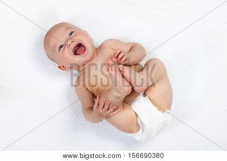 Funny little baby wearing a diaper playing on a white knitted blanket in a sunny nursery. Child after bath or shower on a fresh towel. Infant nappy change and skin care. Cute kid playing with his feet