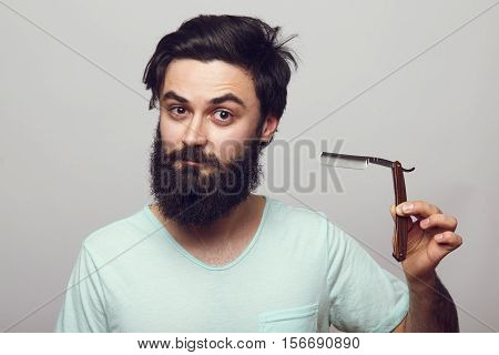 Hipster man with a beard does not want to shave. Bearded young man holding a razor in his hand over a grey background