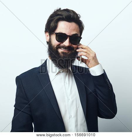 Young bearded confident businessman talking on his cellphone over white background