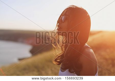 Pensive relaxed girl thinking and looking forward over sunset background. Sunlight filter effect