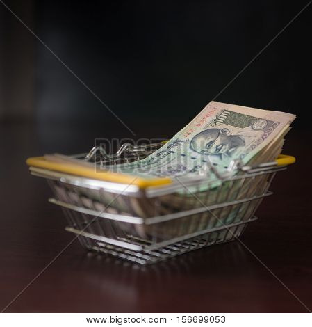 Heap of hundred indian rupee currency notes collected in a small shopping basket. Conceptual image.