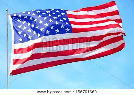 Ruffled American flag on blue sky background.