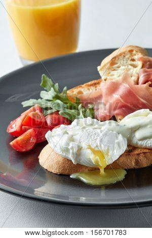 Eggs Benedict with ham and tomato on toast and orange juice