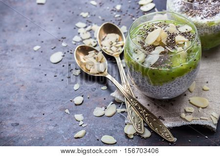 Healthy chia seed pudding with almond milk and fresh fruit topping on a rusty black table. Selective focus, copy space background
