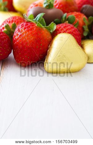Strawberries and chocolate bonbons on white wooden table.copyspace