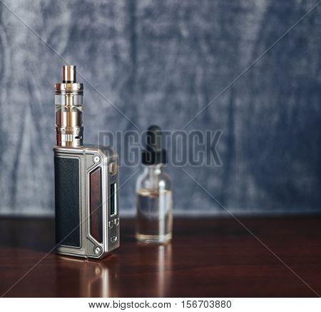 Vape devices, E-cigarette for vaping, liquid in the bottle on wooden table