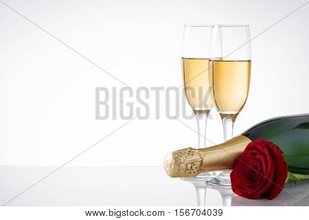 Champagne bottle, cup and red rose on white background