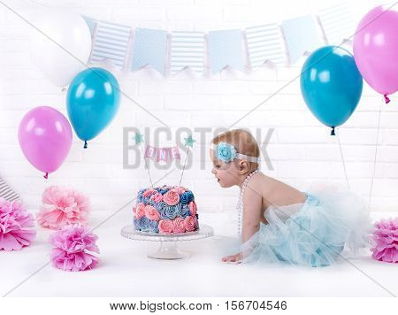 year-old girl in a blue skirt with a bandage on his head sits near a cream cake pink and blue