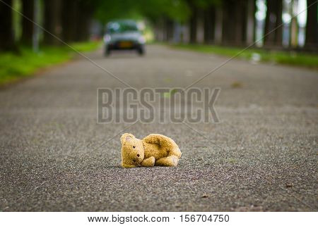 Еeddy teddy bear lies on the road