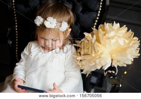 Bonny ruddy toddler sitting in the chair and enthusiastically looking at smartphone screen. In white dress with a wreath on his head the child like an angel.