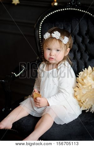 Ruddy toddler sits in a beautiful chair and eats cookies. In a white dress with a wreath on the head and barefoot the baby is similar to an angel. The room is festively decorated.