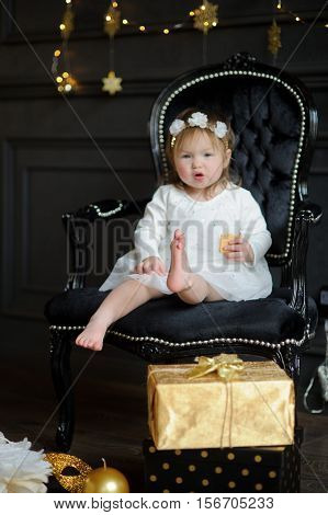 Little ruddy girl sits in a beautiful chair and eats cookies. Toddler is dressed in an elegant white dress. On the head of the girl a wreath. Room is festively decorated on floor boxes with gifts lie