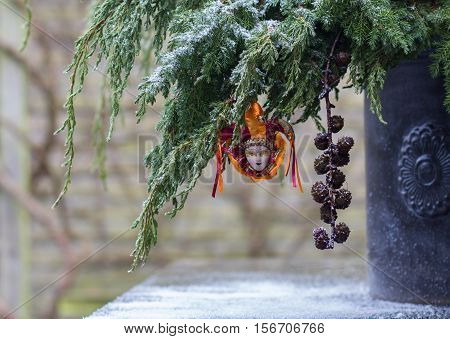 Fir branch on snow with decoration venetian harlequin in the garden
