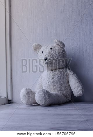 Forgotten old fashioned teddy bear sitting alone home