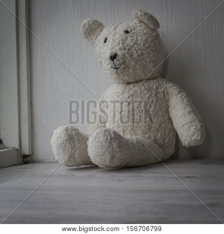 Old age concept. White teddy bear sitting sad one in the window