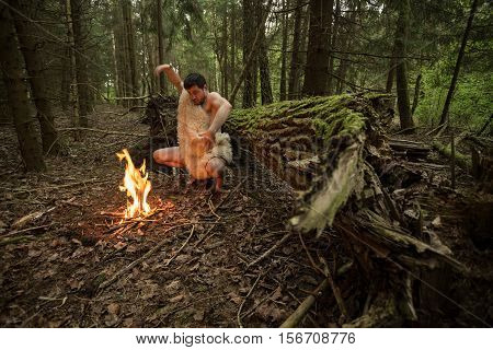 Caveman in animal skin kindles a fire in the forest