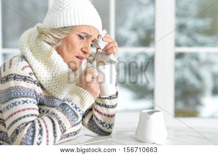 Portrait of senior woman with cup of tea feels sick sitting at the table