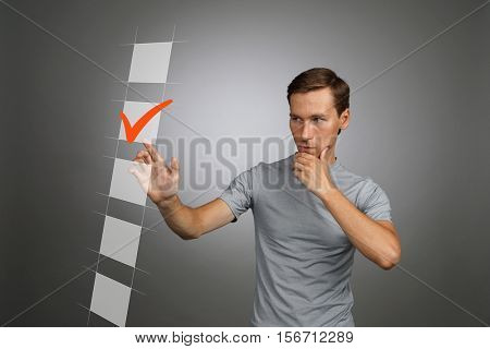 Young man in t-shirt checking on checklist box. Gray background.