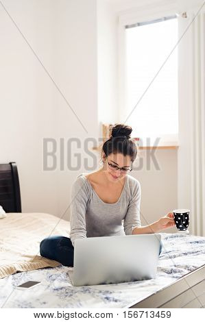 Beautiful young woman sitting on bed, working on notebook, holding a cup of coffee or tea, home office.