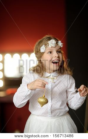 Christmas. Elegantly dressed girl of 8-9 years with delight admires gold Christmas garlands and Christmas-tree decorations. They shine a magic light. Christmas-the mysterious and wonderful time.
