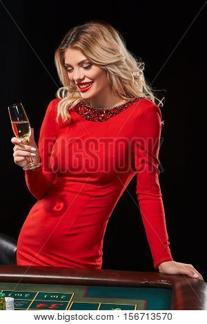 blonde girl in a red dress with a glass his hand playing Roulette. Addiction to the gambling