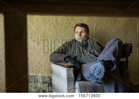 Abandoned destroyed house destroyed interior skinned walls a man with a gun in the house