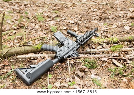 Automatic rifle m16 lying on the ground in the forest lies in the forest the dry leaves and pine forest