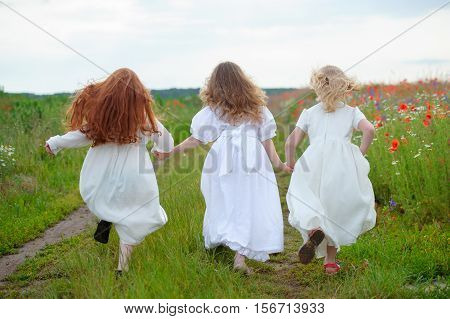 running children outdoor. Three teenage girls runaway