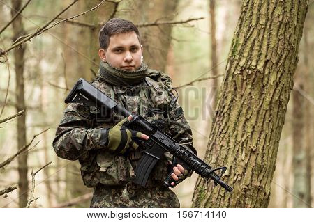 soldiers in the coniferous forest with a gun aiming ready for battle