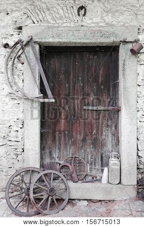 Rural historic door, two saws and two wooden spoked wheels