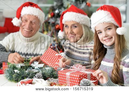 Portrait of happy grandparents with granddaughter in Santa hats with Christmas presents