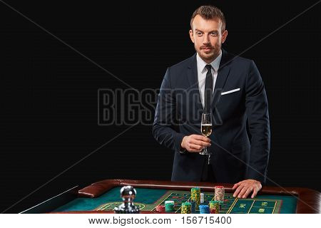 man in a suit playing roulette. addiction to gambling. In the hands of a glass