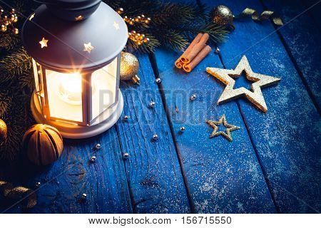 Christmas Lantern with decorations on blue wooden background. Studio shot