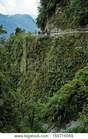 Cyclists sitting down on the Death Road - the most dangerous road in the world. October 4, 2012 - North Yungas Bolivia.