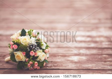Beautiful wedding bouquet on wooden background, vintage toned, copyspace. Marriage concept