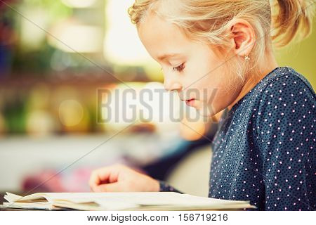 Little girl with school book is doing his homework for elementary school.