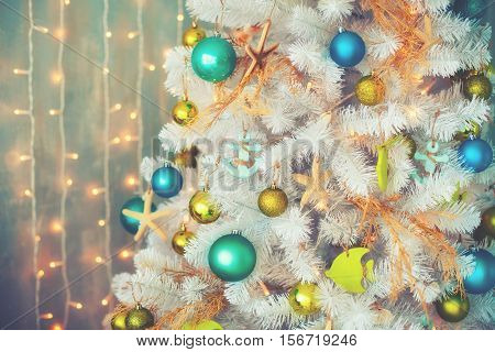 White decorative x-mas tree with colourful balls, vintage toned, christmas concept