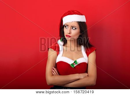 Offended Unhappy Woman In Trouble With Folded Arms On Empty Copy Space In Christmas Costume On Red B